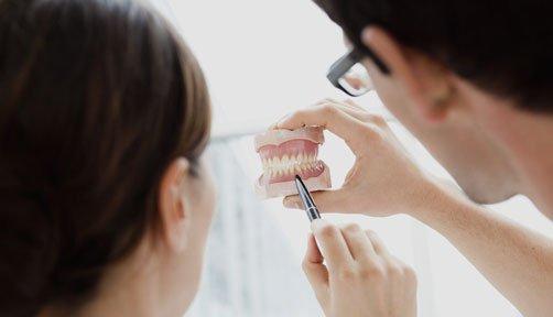 Dentist pointing at dentures